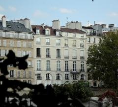 Immeuble - Français:   La toiture et la façade de cet immeuble donnant sur le quai d\'Orléans de l\'Ile Saint Louis, à Paris, sont inscrit au titre de monument historique depuis 1988, mais ce sont les ferronneries la chose plus remarquable de la façade. La photo est prise depuis le square du Mémorial des Martyrs de la déportation.