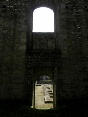 Abbaye de Coatmalouen - Abbaye Notre-Dame de Koad Malouen, commune de Kerpert (22). Intérieur de l'abbatiale. Revers de la façade du transept sud. Porte vers le cloître.