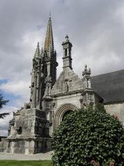Eglise Notre-Dame et Saint-Tugen - Église Notre-Dame et Saint-Tugen de Brasparts (29). Flanc sud. Calvaire, porche et clocher.