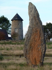 Ensemble mégalithique dénommé alignements de Cojoux - English:  The windmill of Cojoux and one of the Menhir, flame-shaped, from the south stone row of Moulin's (Mill's) alignments in the Landes de Cojoux (Cojoux's moorland) , Saint-Just, Brittany, France.