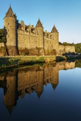 Château - English: Josselin Castle. Taken from the bridge across the river Oust in Josselin on a very calm August evening. The château was lit with golden sunlight and reflected in the relatively still water. About 30 frames, in five rows, were combined in PtGui to produce this 150 megapixel stitched image. I used a 50mm lens (on a 1.5x crop camera) and Nodal Ninja 3II panoramic head on top of a Benro C1282TV1 Travel Angel II tripod. The resulting image is similar to that produced by a lens with 16mm focal length on my crop camera (24mm full frame), but much much more detailed. Stitching the bottom row of frames was difficult as the software generated no automatic control points. With only the surface of the water in these frames, reflections are distorted by ripples and surface features are shifted by the downward movement of the river. Smartblend did a better job than PtGui's own blend tool in handling such movement and discontinuities in the ripples. Other sizes:  50% (37.5MP) 40% (24MP) 30% (13.5MP) 20% (6MP)