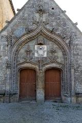 Eglise Saint-Golven et son calvaire - Français:   Le tympan prend une forme d\'accolade, ainsi que le linteau de chacun des deux vantaux. Des motifs végétaux ornent l\'ensemble.