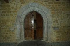 Eglise Saint-Michel - Français:   Le portail de pierre est un arc brisé et il présente quelques arcs moulurés et une archivolte ornée de têtes et d'écus avec des croix à six branches et des fleurs de lys. Cette décoration et les arcs font de cette porte une oeuvre tardive.