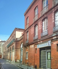 Immeuble - English:  Rue Clémence-Isaure, in Toulouse - N ° 2bis Neoclassical building. The plan is symmetrical: the hotel has, on the street, a romantic facade element, with arched windows, adorned with ironwork. A porch surmounted by a balustrade leads to a courtyard. The two guard posts at the entrance, and an overhead metal raceway, connect the East and West building wings.
