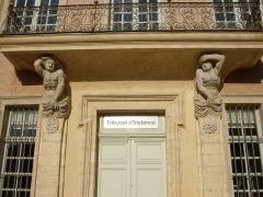 Ancien évêché -  Atlante et cariatide soutenant le balcon (XVIIIe siècle) de l'ancien évêché d'Uzès, aujourd'hui le Tribunal d'Instance.