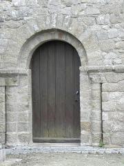 Eglise et cimetière qui l'entoure - Français:   Porte romane du transept sud de l\'église Notre-Dame de Genêts (50).
