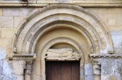 Eglise d'Ouézy - Français:   Portail nord, dans le tympan, représentation d\'un moine couché et dormant, église Saint-Pierre d\'Ouézy (Calvados)