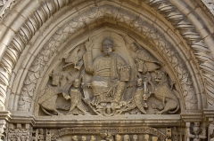 Eglise Saint-Hilaire -  Tympanum of the west porch: A Christ in Glory sit down on a mandorla held by two angels with crossed wings, surrounded by the tetramorph.