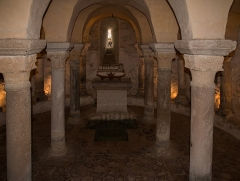 Prieuré - English:  Colonnade of the main apse of the crypt. At the foot of the altar excavations were carried out to find traces of relics of children that would have been buried there.