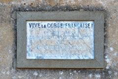 Immeuble dit Maison forte -  Centuri, Cap Corse (Corse) - plaque commémorative sur la façade principale de la chapelle de la confrérie des Pénitents de la Sainte-Croix (de l'ensemble paroissial Saint-Sylvestre inscrit MH), apposée à la veille de la Seconde Guerre mondiale.