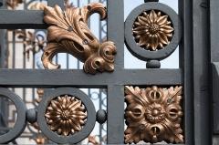 Ancienne manufacture nationale d'armes de Saint-Etienne -  Lilies flowers and buttons enhance the large wrought iron gate.
