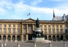 Immeuble (ancienne douane) -  Place Royale de Reims avec la statue de Louis XV par Cartellier (1818); les groupes du piédestal sont de Pigalle (1765). Le plan de la place a été dessiné par Jean Gabriel Legendre; les travaux ont duré de 1756 à 1760. Derrière la statue, on peut voir l'Hôtel des Fermes, qui abrite actuellement la sous-préfecture.
