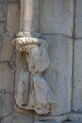 Eglise - Deutsch: Katholische Kirche Notre-Dame-de-Nazareth in Seyne, einer Gemeinde im Département Alpes-de-Haute-Provence in in der französischen Region Provence-Alpes-Côte d'Azur, Portal mit Fragment einer Figur, die eine Säule trägt
