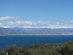 Eglise Notre-Dame de la Garoupe - English: Bay of Antibes, looking to Nice. In the background the montains of Mercantour, with snow in april, Alpes-Maritimes, France. View from la Garoupe