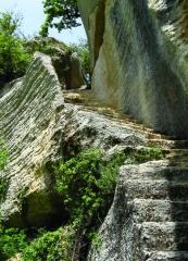 Fort (vestiges du) - Nederlands: De hoogte - een uitloper van het massief van de Luberon - waarop de ruïnes van Fort Buoux (Buoux, Vaucluse, Provence-Alpes-Côte d'Azur) zich bevinden, kende bewoning vanaf het midden-paleolithicum, over de Keltische en Gallo-Romeinse periode tot in de middeleeuwen. Het fort - de burcht - werd in 1660 geslecht op bevel van Lodewijk de XIVe.  Op de foto een in de rots uitgehouwen trap (vluchtweg?); nu één van de uitgangen van site.