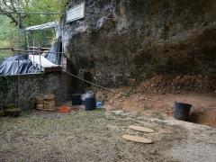 Gisement préhistorique de la Ferrassie - Deutsch: Die Fundstelle La Ferrassie bei Le Bugue in Frankreich. Die ovalen Steinplatten markieren die Fundstellen der Neandertaler-Skelette. Links unter den gestapelten Schlämmsieben die Fundstelle des LF 1.