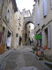 Porte, dite de la Cadène, et maison à pans de bois attenante - Français:   Bâtiment accolé à la porte de la Cadène, Saint-Emilion, Gironde. Bâtiment au centre de l\'image sur le coté gauche de la rue.