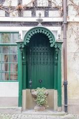 Maison - English: Abri sculpté semblable à une porte en bois servant d'abri et de robinet pour la plante située en son milieu.