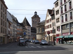 Tour - English: Looking through rue des Bouchers in Strasbourg, with the medieval gate-tower of the Hôpital civil and the rotunda of the Ancienne école de médecine in the background