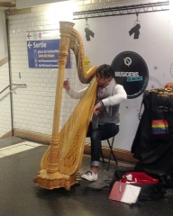 Métropolitain, station Châtelet - English:  A harpist performing in the Paris Metro Chatelet station in the passageways between the #1 and #4 lines.