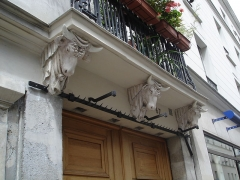Boutique -  67 rue de Turenne in Paris 3e arrondissement: Balcony held by 3 cow heads. This was the location of a butcher before the first World war. We can still see the hooks for the carcasses