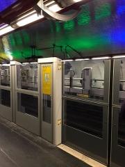 Métropolitain, station Nation -  De metro's die hier arriveren en vertrekken, rijden zonder bestuurder. Mede daarom zijn op de stations ter bescherming van de reizigers wanden met deuren langs de perrons geplaatst.
