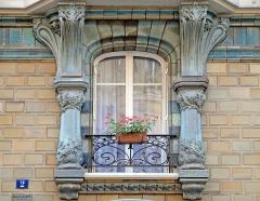 Immeuble Les Chardons - Fenêtre de l\'immeuble conçu en 1903, situé au 2 rue Eugène-Manuel à Paris, par l\'architecte Charles Klein et le céramiste Emile Muller.  L\'édifice très coloré en bleu-vert et ocre est du plus beau style art nouveau. Il est recouvert de grès flammé en céramique avec une décoration déclinant les chardons (inspirée du peintre Eugène Grasset) .  L\'immeuble est inscrit à l\'inventaire des Monuments historiques