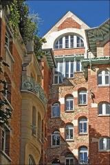 Immeuble dit Castel Béranger - La cour intérieure du Castel Béranger, on peut y observer la variété des matériaux utilisés: briques, meulières et pierres de taille et le travail spécifique effectué sur les parties hautes du bâtiment.  Le Castel Béranger est un immeuble de rapport de trente-six appartements situé 14, rue La-Fontaine dans le 16e arrondissement de Paris. Il a été conçu par l\'architecte Hector Guimard. Sa construction a lieu à partir de 1895 jusqu\'en 1898. C\'est un chef d\'oeuvre d\'art nouveau français.  Summary  Castel Béranger — Paris. Hector Guimard y applique un principe fondamental de l'Art nouveau: celui de l'unité complète de l'œuvre. Il est également, et comme à son habitude, l\'auteur du second-œuvre et de la décoration intérieure (sols, menuiserie, serrurerie, vitrerie et vitrail, peinture, tapisserie et papier-peint) mais aussi du mobilier. On retrouve à l\'extérieur plusieurs thèmes chers à l\'auteur: le bow-window, la loggia, le balcon et la ferronnerie ouvragée. L'immeuble est primé au 1er concours de façades de la Ville de Paris en 1898, mais cette nomination est critiquée.  extrait de Wikipedia.fr  fr.wikipedia.org/wiki/Castel_B%c3%a9ranger