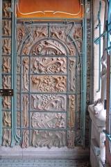 Immeuble dit Castel Béranger - L\'éclairage est ici la lumière naturelle (le porte d\'entrée est à droite sur la photo) ce qui donne une couleur dominante bleue au décor.  Le hall d\'entrée est décoré par de grandes plaques de céramique en grès flammé réalisées par Alexandre Bigot et protégées par des ferronneries peintes en bleu-vert.  Le plafond du hall et les hauts des murs sont recouverts de plaques de cuivre, sur lesquelles ont été placés des motifs en métal.  Un éclairage artificiel a été conçu pour mettre en valeur cet ensemble, ce qui donne l\'impression de pénétrer dans une grotte envahie par la végétation.   fr.wikipedia.org/wiki/Alexandre_Bigot_%28c%C3%A9ramiste%29