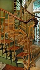 Immeuble dit Castel Béranger - Français:   L\'escalier principal du  Castel Béranger: Paris. Des briques de verre soufflé (au fond derrière l\'escalier), inventées par l\'architecte Georges Falconnier, ont été utilisées par Hector Guimard pour éclairer et décorer la cage de l\'escalier principal dont on voit au premier plan la rampe en fer forgé et son décor art nouveau.