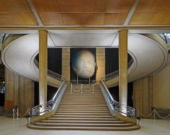 Palais d'Iéna, ancien Musée des Travaux Publics, actuel Conseil économique et social -  Le portrait d'Auguste Perret, dans le grand escalier du palais d'Iéna L'escalier fait face à l'entrée de la salle de conférence, il sert de charnière entre les extrémités des ailes nord et sud du Palais. On remarque que les colonnes en béton armé sont effilées vers le bas pour exprimer