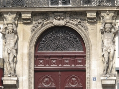 Immeuble - English: Atlantes above the entrance of the 2 place d'Estienne d'Orves near the church of the Holy Trinity, 9th arr. Paris. Building built in 1866 by Jean-Charles Forrest. The atlantes sculpted by Joseph-Michel Caillé (1836-1861) have an egyptian looking and wear at the waist a skin of lion.