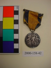 """Manoir de la Haye -  Accession: 2000-158-42 Award, Medal, Olympic, Silver, Captain C.T. Osburn 3.01"""" H X 1.77 W Silver Olympic medal from the Stockholm Olympics in 1912. This was the first Olympics where all five continents were represented, with a total of 265 competitors. The Olympics opened on May 5 1912 and closed on May 27 1912. The medal features a herald proclaiming the opening of the games with a statue of Ling founder of the Swedish medical gymnastic system. Captain Osburn competed in three successive Olympic games and won a total of 11 Olympic medals. He won two silver medals at the 1912 games, 600m free rifle, and army rifle 300m 3 positions. The edge of the medal is engraved with , """"C.T. Osburn, military rapid fire.""""  Collection of Curator Branch, Naval History and Heritage Command."""