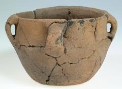 Tumulus surmonté de menhirs, dit le Château Bû - Français:   Site: Château Bû à Saint-Just  Vase biconique à cinq anses. Le fond est plat; le profil est légèrement carèné. Le bord est faiblement ourlé. La pâte est à dégraissants moyens. Il porte à l\'intérieur des traces de feu. Vase issu de la tombe de l\'Age du Bronze n°1. Celle-ci s\'appuie sur le grand menhir dominant le tumulus. Le vase était situé à l\'Ouest de la tombe. Hauteur en cm 10,8 Diamètre en cm 10,2 (fond)  Diamètre en cm 14,5 environ
