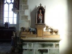 Chapelle Saint-Eloi - Français:   retable de la chapelle Saint Eloi de Guiscriff (Morbihan). une statue en bois polychrome du saint ferrant un cheval et des ex-voto de chevaux en bois sont visibles.