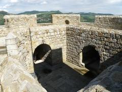 Ruines de la tour du château fort - Français:   Montpeyroux (Puy-de-Dôme). Donjon (XIIe siècle), sommet de la tour. Remarquer dans le lointain, au centre, la silhouette du château ruiné de Burin. Dans le créneau du milieu, en contrebas à gauche du château de Burin: partie du village de Parent. Coup d\'œil vers l\'est.