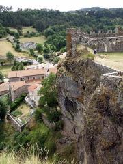 Restes du Château fort -  Arlempdes, comm. de la Haute-Loire, France (région Auvergne).   Vue du château depuis la chapelle castrale. Nous regardons vers le sud-ouest. En haut à droite: courtine sud-ouest entre les tours d'angle sud (à gauche) et ouest (contre le bord droit de la photo). On voit que la falaise penche nettement vers la gauche, et que le château est construit en surplomb au-dessus de la Loire (qui coule dans les profondeurs en bas à gauche, non visible sur la photo). Maisons de la bourgade d'Arlempdes au centre gauche.