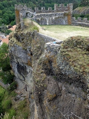 Restes du Château fort - Français:   Arlempdes, comm. de la Haute-Loire, France (région Auvergne).  Vue du château depuis la chapelle castrale. Nous regardons vers le sud-ouest. En haut: courtine sud-ouest entre les tours d\'angle sud (à gauche) et ouest (à droite). On voit que la falaise penche nettement vers la gauche, et que le château est construit en surplomb au-dessus de la Loire (qui coule dans les profondeurs en bas à gauche, non visible sur la photo). Maisons de la bourgade d\'Arlempdes en haut à gauche.