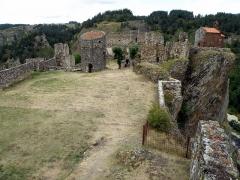 Restes du Château fort - Français:   Arlempdes, comm. de la Haute-Loire, France (région Auvergne).  Vue du château depuis la tour d\'angle sud (nous regardons donc vers le nord-est). A l\'avant-plan, esplanade constituant la moitié sud de la forteresse. La grosse tour circulaire au bout de cette esplanade, ainsi que les débris de mur à gauche de la tour, séparent la forteresse en deux moitiés, nord et sud. Le pan de muraille au fond (avec un crépi sur sa partie inférieure) est le seul vestige subsistant de l\'ancien logis seigneurial. En haut à droite, chapelle castrale, coiffant une falaise basaltique penchée, au pied de laquelle on distingue, tout en bas à droite, un peu des eaux de la Loire. A l\'horizon à gauche, fermes du hameau d\'Espinasse (comm. de Salettes).