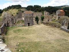 Restes du Château fort - Français:   Arlempdes, comm. de la Haute-Loire, France (région Auvergne).  Château: esplanade formée par la partie sud de la forteresse. Vue prise depuis le chemin de ronde sur la courtine sud-ouest, près de la tour d\'angle sud. Contre le bord gauche de la photo: partie nord-ouest de la muraille d\'enceinte. La grosse tour circulaire au centre, ainsi que le restant de mur à gauche de cette tour, séparent la forteresse en deux moitiés, nord et sud. Le pan de muraille au fond (avec un crépi sur sa partie inférieure), derrière la tour ronde, est le seul vestige subsistant de l\'ancien logis seigneurial. Chapelle castrale à l\'extrême droite, posée sur une falaise basaltique penchant au-dessus de la Loire. Coup d\'oeil vers le nord-est.