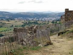 Ruines du château fort - Français:   Forteresse de Polignac, dans la commune de Polignac, Haute-Loire, France (région Auvergne). Segment méridional de la muraille d\'enceinte de la forteresse. À l\'arrière-plan, ville du Puy-en-Velay: la masse gris sombre de la cathédrale, avec son haut clocher et sa coupole de croisée, ainsi que le rocher Corneille portant sa statue de la Vierge (en rose), sont visibles à gauche. Vue vers le sud-est.