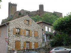 Ruines du château fort - Français:   Forteresse de Polignac, dans la comm. de Polignac, Haute-Loire, France (région Auvergne). Partie nord de la muraille d\'enceinte, aperçue depuis la place de l\'église. Entre le donjon à gauche (tour carrée) et la tour d\'angle circulaire au centre (dite tour de la Géhenne): porte d\'entrée de la forteresse (rainures pour recevoir les bras du pont-levis). Tout à droite: bâtiment du corps de garde nord.