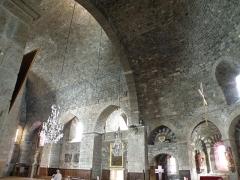 Eglise Saint-Georges -  Saint-Paulien, dép. de la Haute-Loire, France (Auvergne). Église paroissiale Saint-Georges: nef (voûte en berceau, à gauche) et choeur (voûte en cul-de-four, à droite).