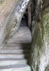 Eglise Notre-Dame et croix de pierre -  Entrée de l'église Semi-rupestre de Vals (Ariège), dont la partie inférieure est creusée dans le poudingue.