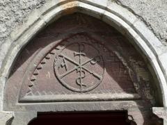 Eglise Notre-Dame - Français:   Tympan orné d\'un chrisme, au-dessus de la porte de l\'église Notre-Dame, Arreau, Hautes-Pyrénées, France.