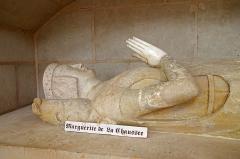 Eglise (église Saint-Pierre et collégiale Saint-Michel réunies) -  Bueil-en-Touraine (Indre-et-Loire)   Collégiale Saint-Pierre, Saint-Michel et Saints-Innocents (XIIe, XIVe, XVe, XVIe siècles)   Gisant du XVe siècle, de Marguerite de Chausse (de la Chaussé, de la Chausséee, née vers 1375, † après 1443), épouse de Pierre de Bueil, sous un enfeu. Pierre pour le corps et marbre pour la tête et les pieds. Gisant caché à la révolution et redécouvert en 1868.  Marguerite de la Chaussée s'est mariée vers 1390, avec  Pierre de Bueil, Chambellan du Roi Charles VI, seigneur de la Motte-Souzay, fils puiné de Jean IV seigneur de Bueil.  Marguerite de la Chaussée survécut longtemps à son mari et fut inhumée à côté de lui dans l'église collégiale de Bueil.  Les petits chiens aux pieds de la statue sont un symbole de fidélité. On retrouve les mêmes petits chiens et le même drapé de la robe aux pieds du gisant de la comtesse de Flandre Marguerite de France, à Saint-Denis (1363).