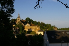 Eglise Saint-Etienne - Face à nous, l'église Saint-Étienne de Château-Renard avec à ses pieds un pan de remparts, prolongés à droite par une tour ronde puis un autre pan de murailles recouvert de verdure. Terminant cette muraille à droite, une pièce rectangulaire et couverte de tuiles, appelée