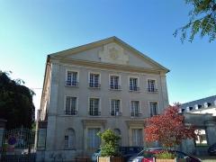 Ancienne abbaye Saint-Taurin - Ancien séminaire, bâtiment annexe à l'église Saint-Taurin, donnant accès au cloître. Occupant: CPAM de l'Eure. Le fronton porte la devise: «Accepit eam in sua» d'Alphonse-Paul-Désiré Gaudron, évêque d'Évreux.