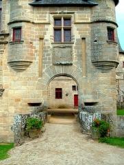 Château de Sedières - Deutsch: Tor und Reste der von Scharwachttürmen flankierten Zugbrücke, darüber ein Steinkreuzfenster, Château de Sédières, Corrèze, Frankreich, 2007