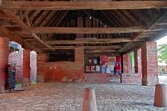 Halle - Collonges-la-Rouge (Corrèze)  La halle date des XVIe et XVIIe siècles.  La halle aux grains et aux vins, en grès rouge est couverte d\'ardoises, elle abrite le four banal.   La charpente est probablement du début du 17ème siècle et est signée de MM. Andrieu et Maurice.